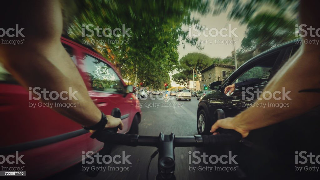 POV commuter riding a road racing bicycle in the traffic stock photo
