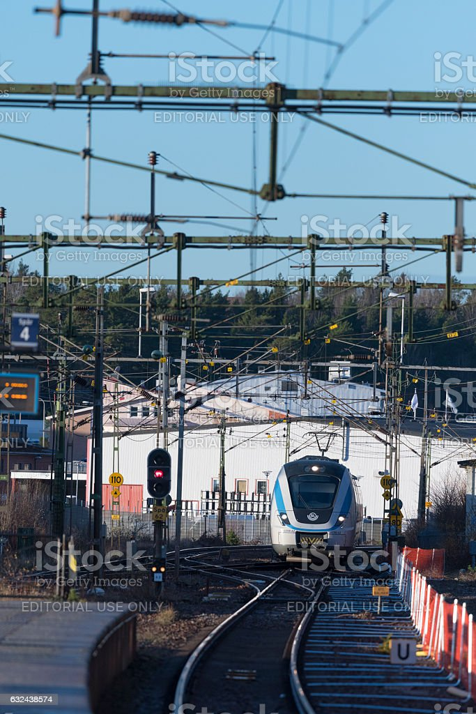 Commuter train approaching the station at Spanga, Stockholm in Sweden stock photo
