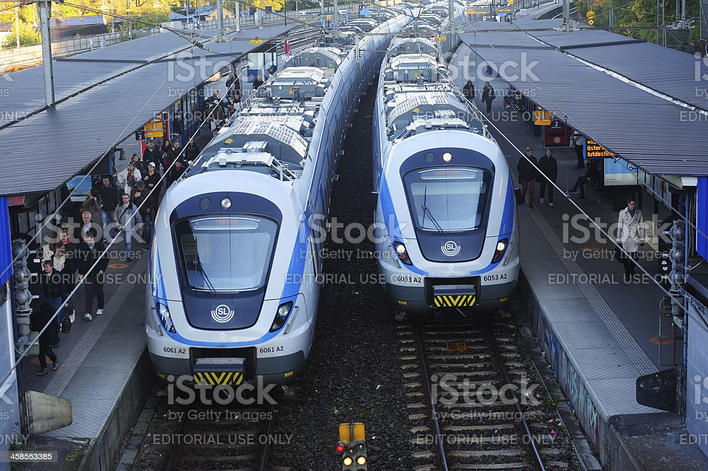 Commuter trains arriving to outdoor station royalty-free stock photo