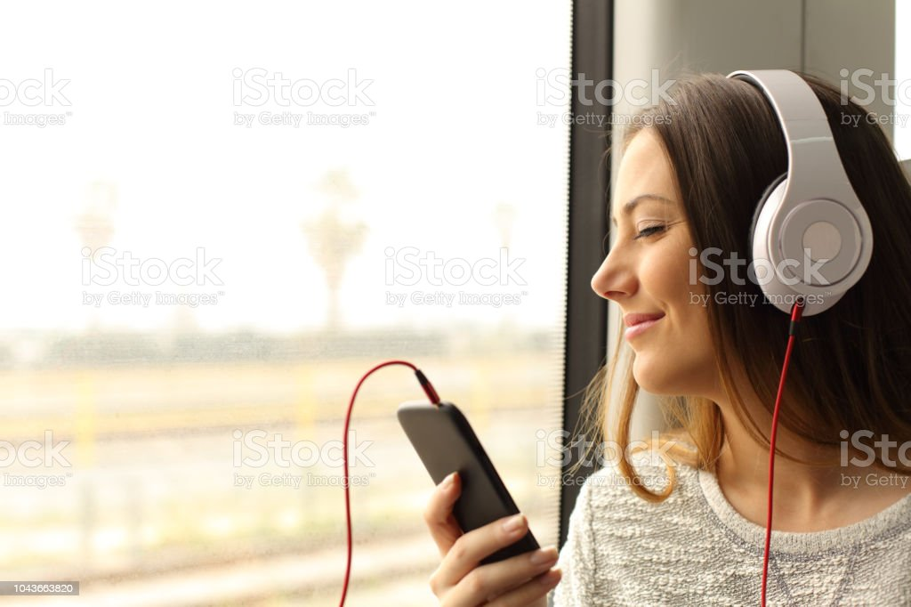 Commuter traveling into a train listening to music stock photo