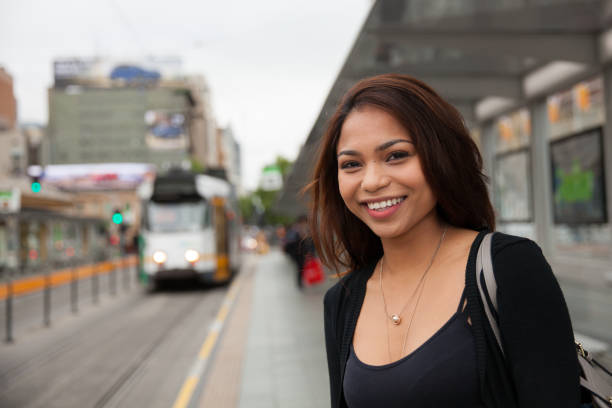 Commuter Waiting for the Tram Female commuter waiting for the tram in downtown Melbourne, Australia. filipino ethnicity stock pictures, royalty-free photos & images