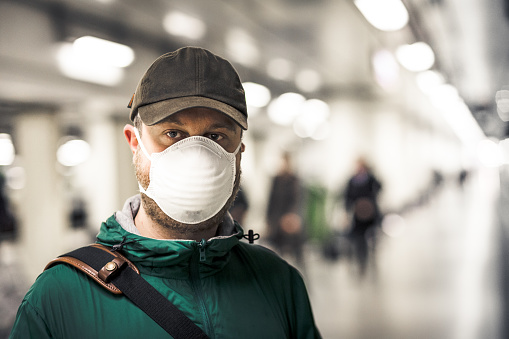 Close up color image depicting a young caucasian man in his 30s wearing a white protective face mask - to protect himself from flu viruses and the coronavirus - standing and waiting for his train on a railroad station platform in the city of London. He is wearing casual clothing, a green rainmack and messenger bag. In the background other people are defocused.