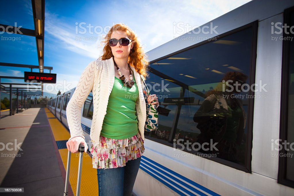 Commuter With a Suitcase in front of Train stock photo