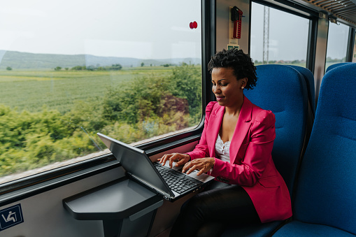 Beautiful African American business woman working on lap top in train while commuting to work