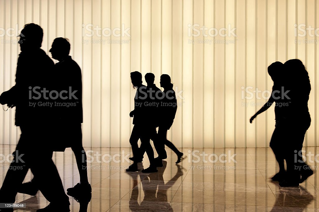 commuters against modern light wall royalty-free stock photo