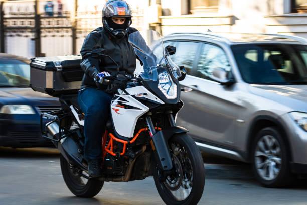 Pendler und Büroangestellte auf dem Motorrad im Berufsverkehr.  Verkehr in der Innenstadt von Bukarest, Rumänien, 2020 – Foto