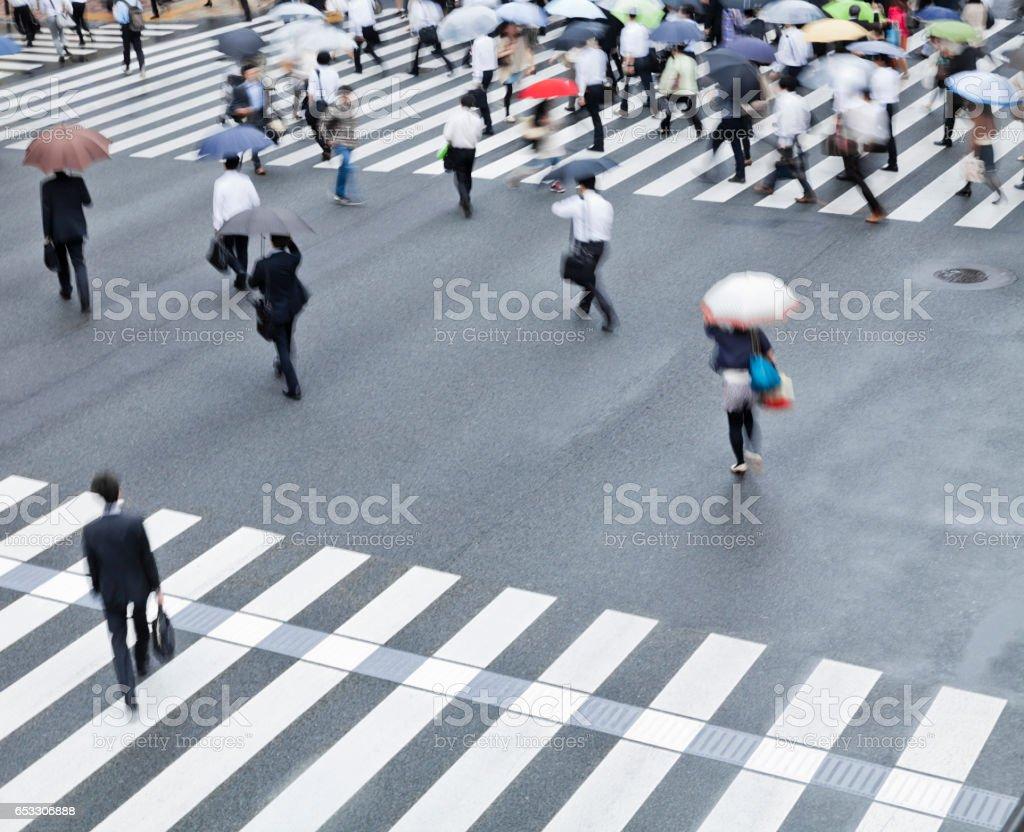 crowds of tokyo city commuters walking through pedestrian walkway on...