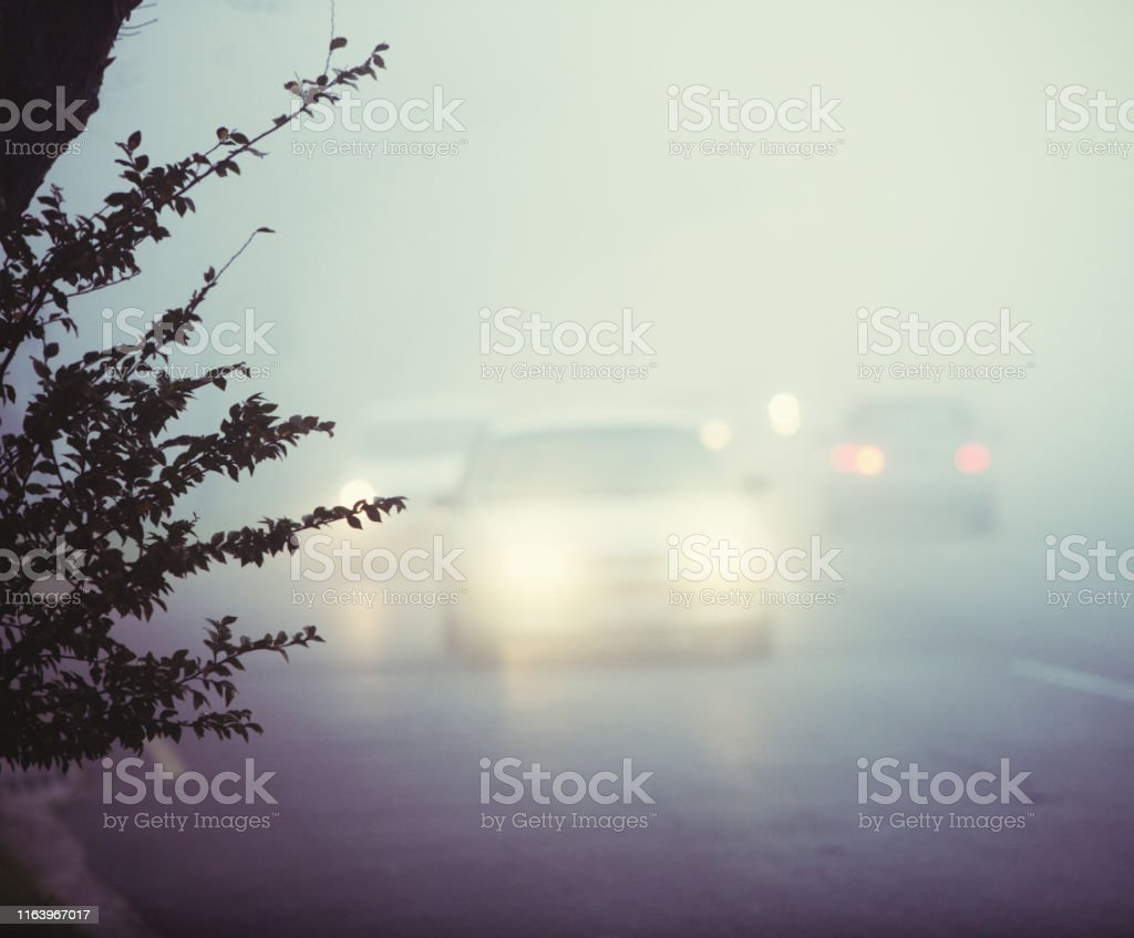 Motor vehicles on a cold, wet morning with headlights on.