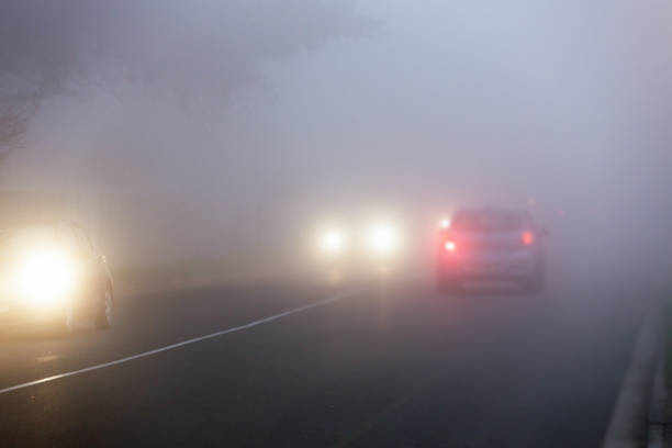 Commuters' cars drive through fog on city street at twilight stock photo
