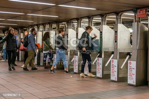New York, USA - May 13, 2018: Commuters going through the turnstiles in a subway station in New York City