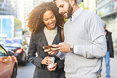 Commuters in the city, business people with a smartphone. Modern business man and woman wearing smart casual clothes in the city. Urban lifestyle