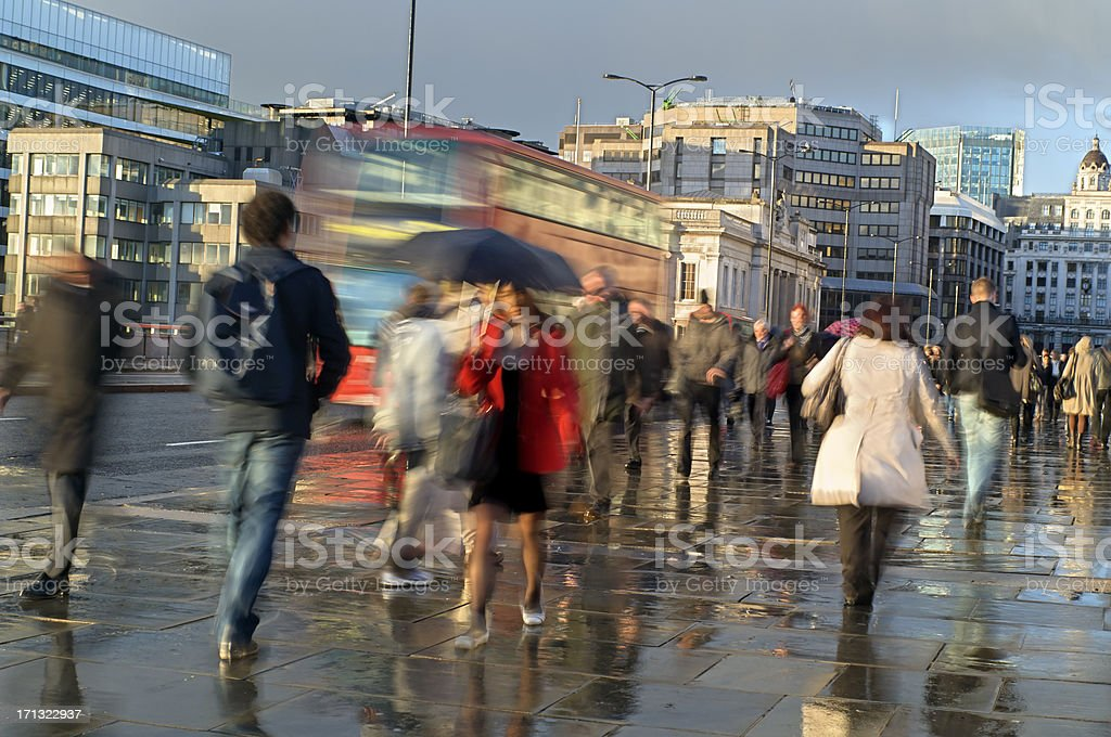 Commuters in the rain walking with umbrellas royalty-free stock photo