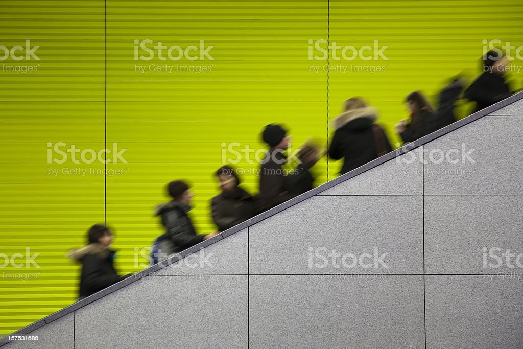 Commuters moving on escalator against a green background stock photo