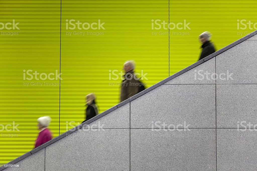commuters on escalator against green background copy space royalty-free stock photo