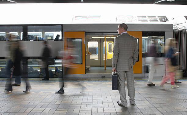 Commuters passing businessman on platform,  (blurred motion) stock photo