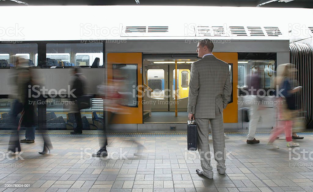Commuters passing businessman on platform,  (blurred motion) stock photo