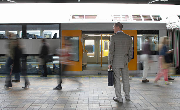 Commuters passing businessman on platform,  (blurred motion) Focus on man. railroad station platform stock pictures, royalty-free photos & images