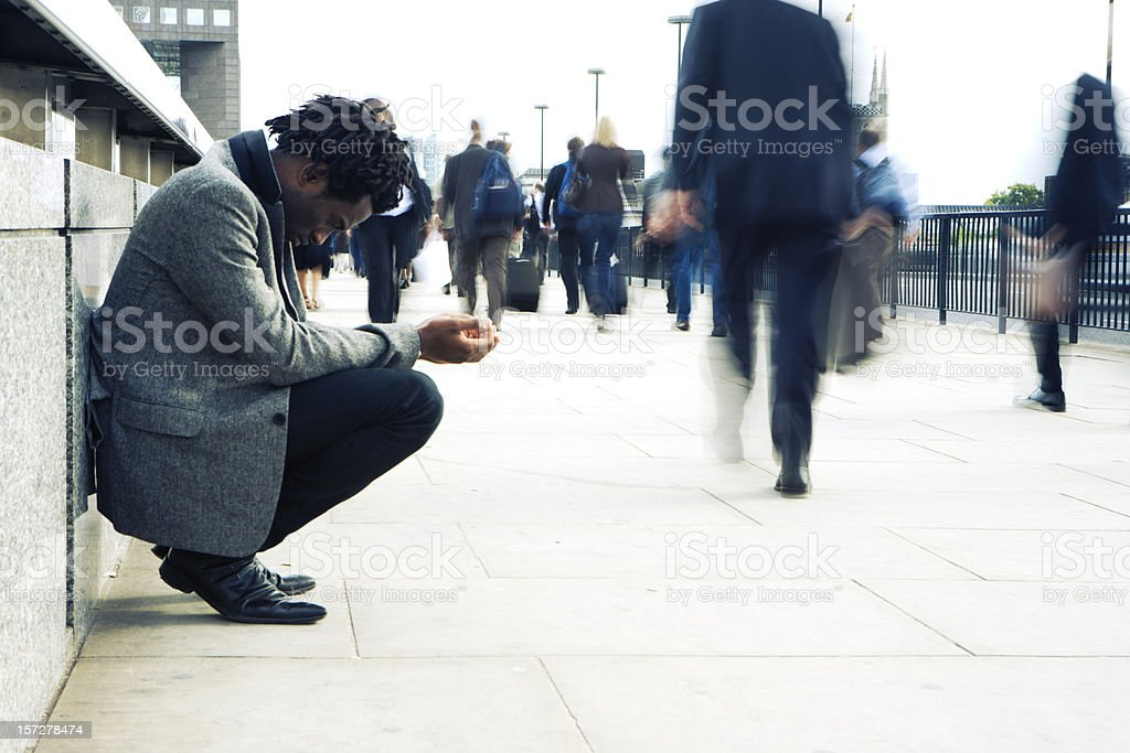 Commuters rushing past a begging character royalty-free stock photo