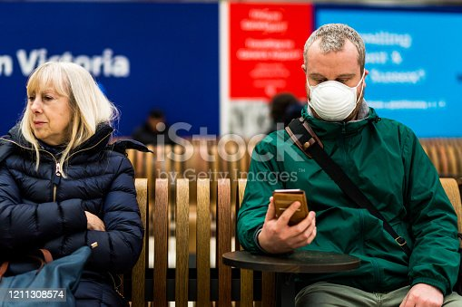 Close up color image depicting a young caucasian man in his 30s wearing a white protective face mask - to protect himself from flu viruses and the coronavirus - sitting and waiting on a bench at a railroad station in the city of London. The man is sitting next to a senior woman in her 60s or 70s, and she is not wearing a face mask. The man is wearing casual clothing, a green rainmack. He is looking at his smart phone. In the background other people are defocused.