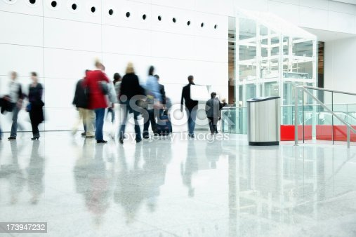 180698194 istock photo Commuters Walking in Modern Corridor, Blurred Motion 173947232