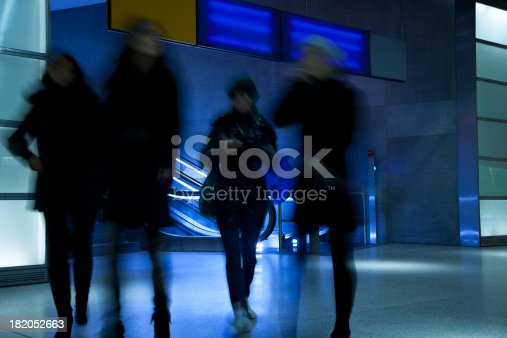 istock Commuters Walking in Modern Glass Interior, Blurred Motion 182052663