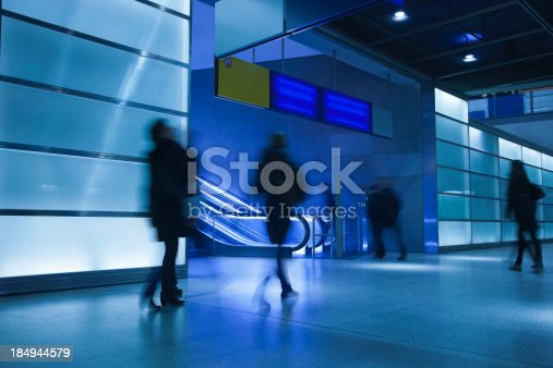 istock Commuters Walking in Modern Glass Interior, Blurred Motion 184944579