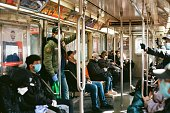 NYC commuters wear protective masks and gloves while riding the downtown 1 Train subway.