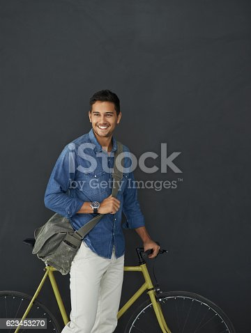 Studio shot of a handsome young man posing with his bicycle against a grey background