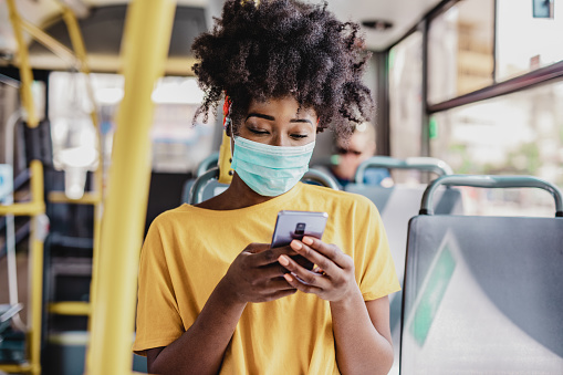 African American woman wearing a protective mask while sitting in a bus and using a mobile phone