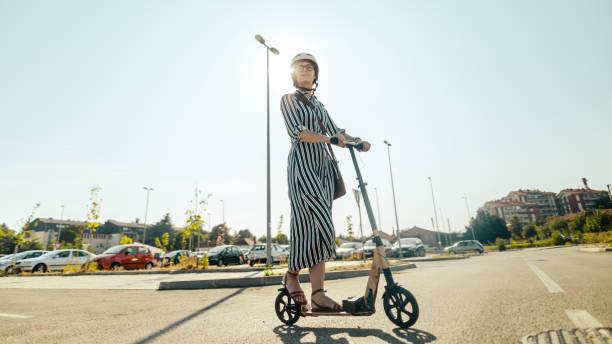 commuting on an electric scooter - monopattino elettrico foto e immagini stock
