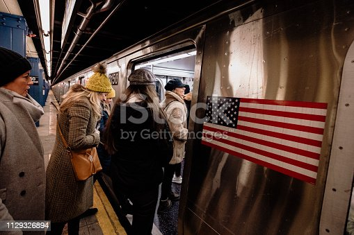 A group of women travelling via subway in New York City. They are boarding the train to go to their next destination.