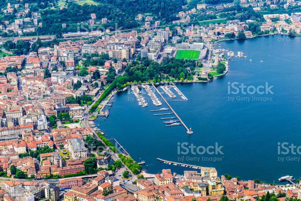 Como city, lake Como, Italy. Aerial view of Como and its lakeside on a beautiful summer day. The port, the public gardens and the train station are visible stock photo