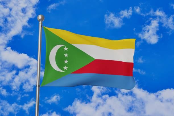 drapeau national des comores ondulant isolé dans le ciel nuageux bleu - comores photos et images de collection