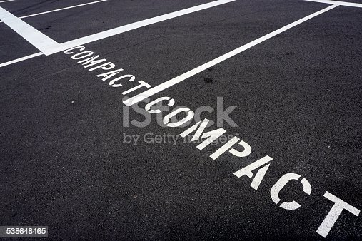 A parking lot is marked with spaces for compact cars