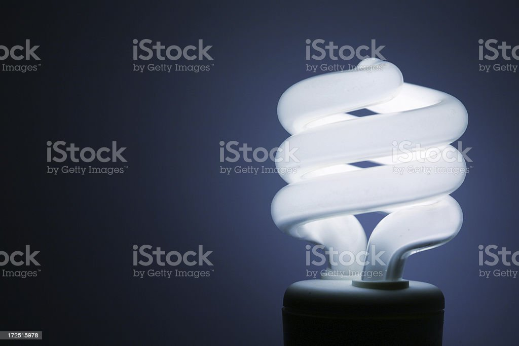 Compact fluorescent lightbulb on dark background stock photo