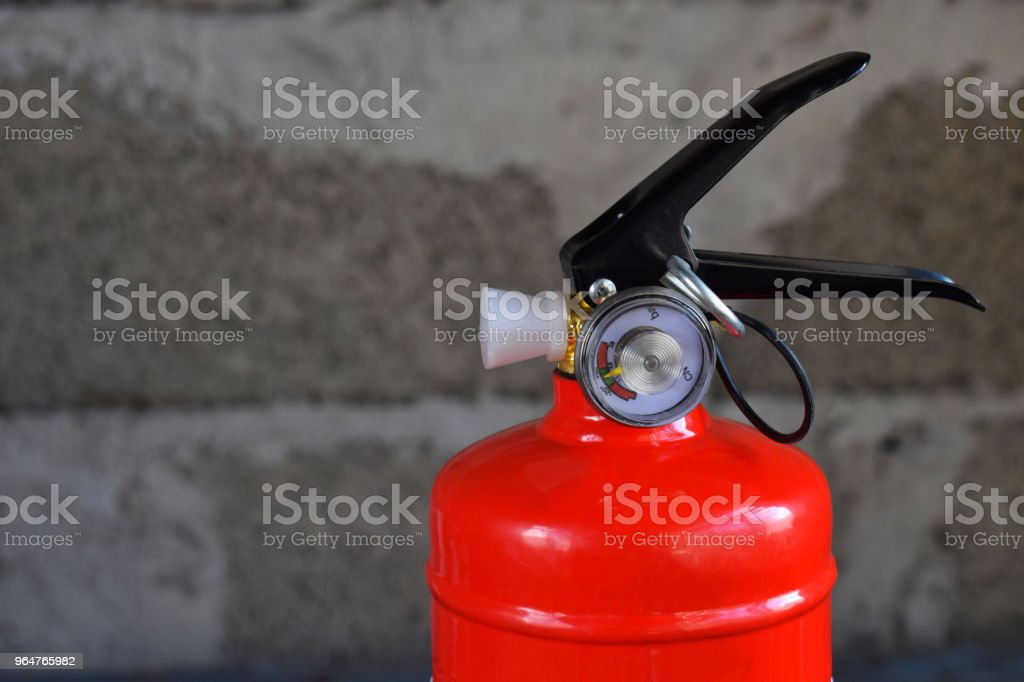 Compact red fire extinguisher for auto or home on grey background. For fire emergencies. royalty-free stock photo