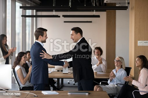 istock Company boss congratulate promoted employee staff applauding 1092087686