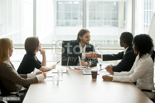istock Company boss handshaking african american employee at corporate group meeting 923039524