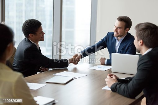 istock Company ceo handshaking african employee at corporate group meeting 1129629355