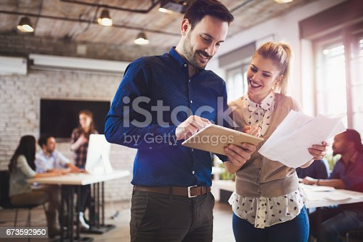 istock Company coworkers working in office and sharing new ideas 673592950