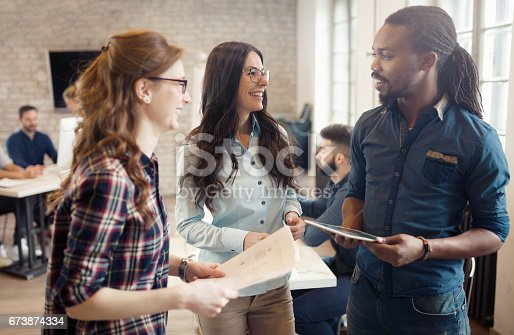 istock Company coworkers working in office and sharing new ideas 673874334