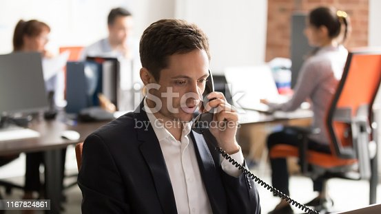 istock Company employee sitting in shared office talking on landline 1167824861