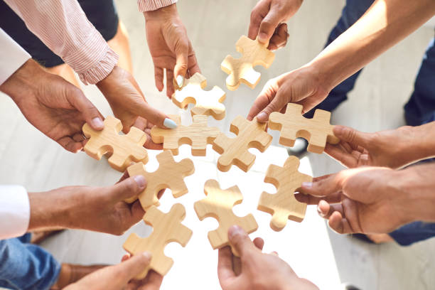 Company employees playing game and joining pieces of jigsaw puzzle during team building activity stock photo