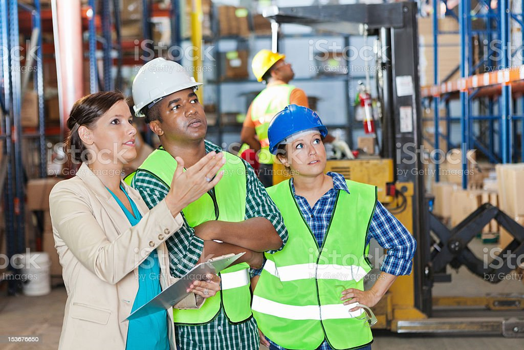 Company executive explaining order to shipping distribution warehouse workers stock photo
