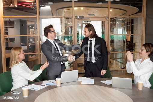 istock Company executive promoting successful manager handshaking while team supporting applauding 954357338