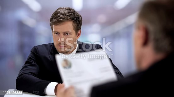 Company HR manager watching through young man resume, job interview concept
