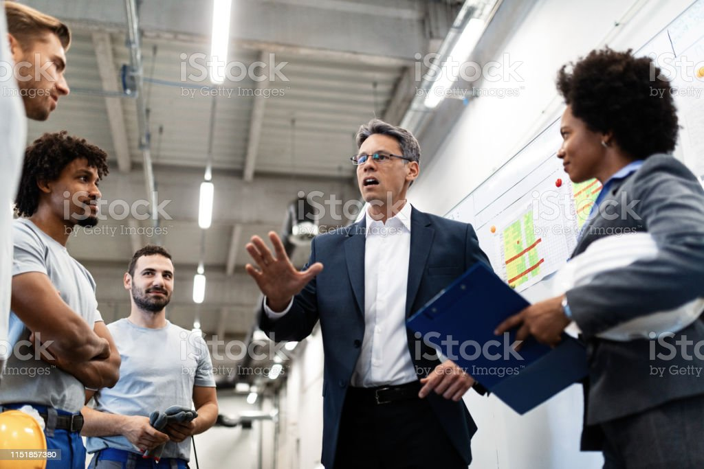 Company leader talking to the employees while visiting a factory. Low angle view of company manager holding a meeting with group of workers while visiting factory. Adult Stock Photo