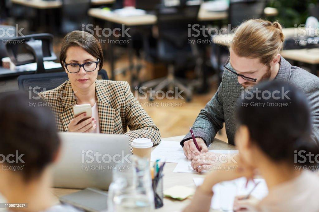 Portrait of modern businesswoman using smartphone during work meeting...