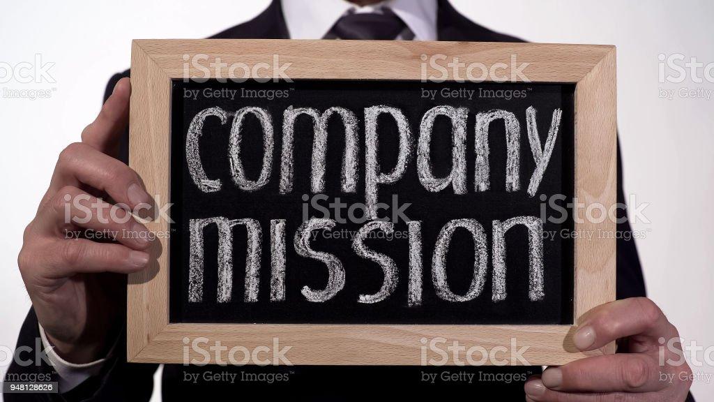 Mission des Unternehmens auf Tafel in Geschäftsmann Hände, Organisation Zweck geschrieben – Foto