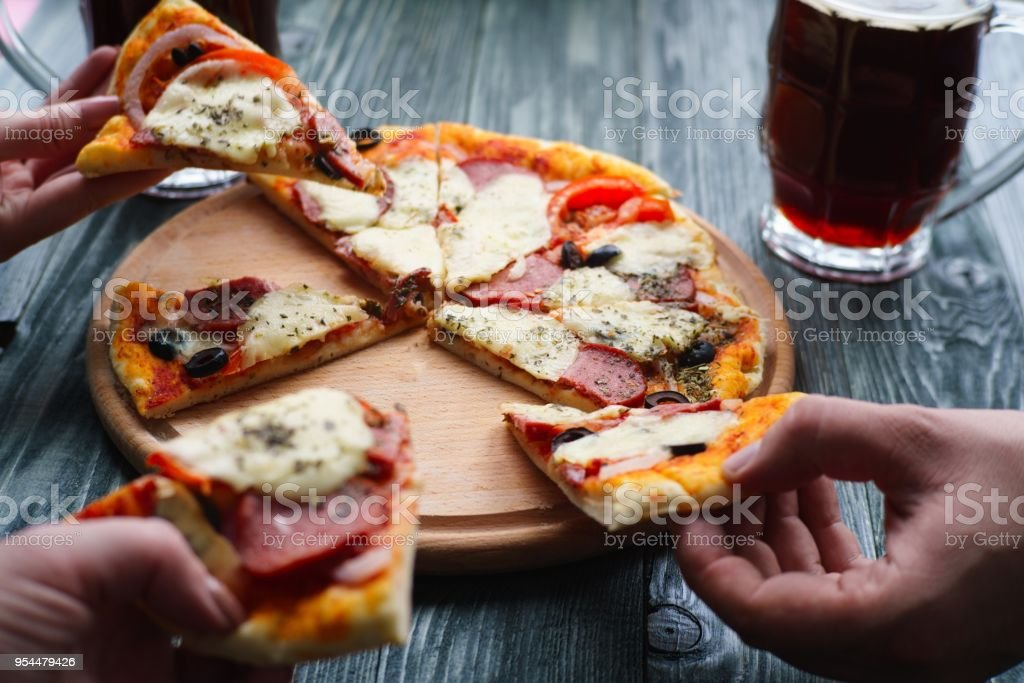 Company Of Friends Eating Homemade Pizza Close Up People